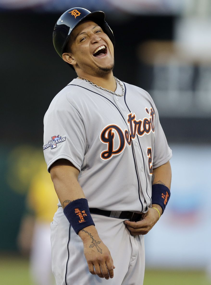 Detroit Tigers third baseman Miguel Cabrera laughs near Oakland Athletics first baseman Brandon Moss in the first inning of Game 2 of an American League  baseball division series in Oakland, Calif., Saturday, Oct. 5, 2013. (AP Photo/Ben Margot)