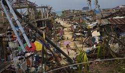 Typhoon Haiyan survivors walk through ruins in the village of Maraboth, in the Philippines on Thursday, Nov. 14, 2013.  Typhoon Haiyan, one of the most powerful storms on record, hit the country's eastern seaboard on Friday, destroying tens of thousands of buildings and displacing at least a half-million people. (AP Photo/David Guttenfelder)
