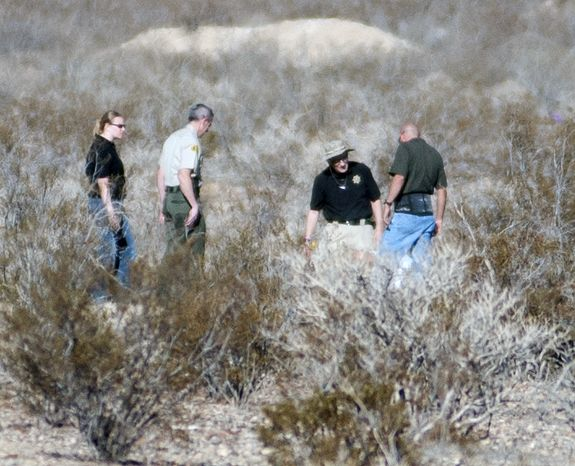 Forensic anthropologists and San Bernardino County Sheriff Department officials investigate two shallow graves where human remains were found in a remote area of Southern California's Mojave Desert in Victorville, Calif., on Wednesday, Nov. 13, 2013. Deputies and coroner's investigators digging through the graves found the remains of four people whose ident