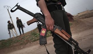 ** FILE ** In this Sunday, March. 3, 201,3 file photo, Kurdish female members, foreground and background, of the Popular Protection Units stand guard at a check point near the northeastern city of Qamishli, Syria. (AP Photo/Manu Brabo, File)