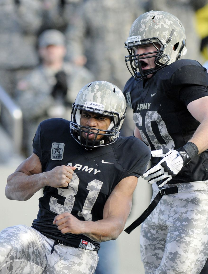 FILE - In this Nov. 9, 2103, file photo, Army's Terry Baggett (31) celebrates a touchdown with teammate Justin Gilbert during the first half of an NCAA college football game against Western Kentucky in West Point, N.Y. Army's camouflage style football uniforms are examples of the latest push by the companies that supply athletic equipment to schools to honor the military. (AP Photo/Hans Pennink, File)