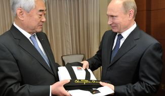 World Taekwondo Federation President Choue Chung-won (left) gives an honorary taekwondo black belt and uniform to Russian President Vladimir Putin at the Lotte Hotel in Seoul on Wednesday, Nov. 13, 2013. (AP Photo/RIA-Novosti, Alexei Nikolsky, Presidential Press Service)