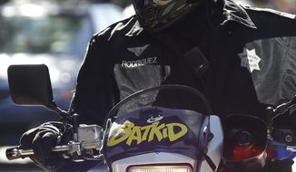 "A San Francisco Police Officer with a Batkid sign on his bike waits for the arrival of Miles Scott, dressed as Batkid, in San Francisco, Friday, Nov. 15, 2013. San Francisco turned into Gotham City on Friday, as city officials helped fulfill Scott's wish to be ""Batkid."" Scott, a leukemia patient from Tulelake in far Northern California, was called into service on Friday morning by San Francisco Police Chief Greg Suhr to help fight crime, The Greater Bay Area Make-A-Wish Foundation says. (AP Photo/Jeff Chiu)"