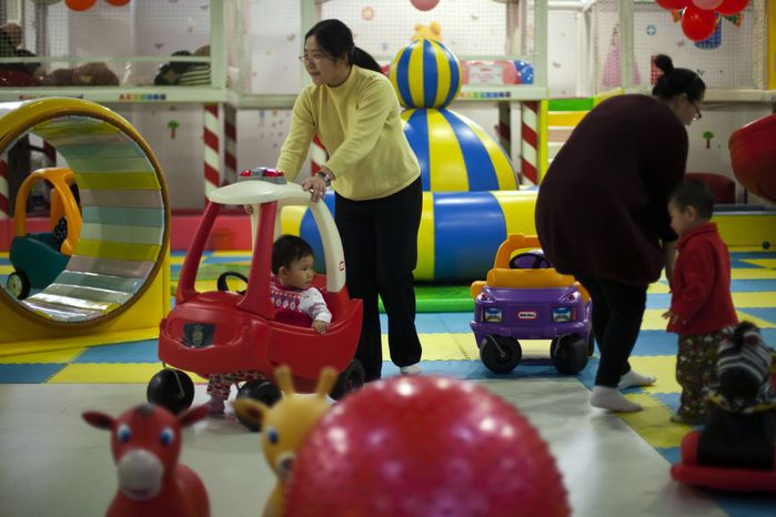 FILE - In this Jan. 10, 2013 photo, parents play with their children at a kid's play area in a shopping mall in Beijing.  China will loosen its decades-old one-child policy and abolish a much-criticized labor camp system, its ruling Communist Party said Friday, Nov. 15, 2013. The official Xinhua News Agency said the party announced the changes in a policy document following a key, four-day meeting of party leaders that ended Tuesday in Beijing. (AP Photo/Alexander F. Yuan, File)