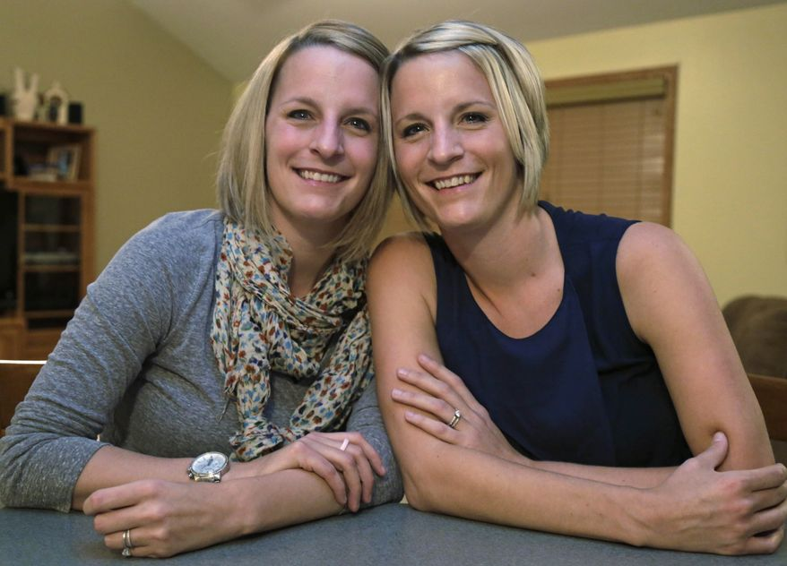 This Monday, Nov. 11, 2013 photo shows identical twins Kristen Maurer, left, and Kelly McCarthy at Kelly's mother-in-law's house in Beecher, Ill. The 34-year-old sisters from Crown Point, Ind., have shared a lot in their lives so when Kelly was diagnosed with breast cancer in 2011, she urged Kristen to get tested, too. Kristen also was diagnosed with breast cancer. Now the twins are sharing a medical rarity: Kristen donated skin and fat tissue for Kelly's breast reconstruction surgery that was performed at the University of Chicago Medical Center by breast cancer surgeon, Dr. David Song on Tuesday, Nov. 12. (AP Photo/M. Spencer Green)