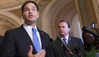Sen. Marco Rubio (left), Florida Republican, accompanied by Sen. Mike Lee, Utah Republican, speaks during a news conference on Capitol Hill in Washington. (Associated Press) ** FILE **