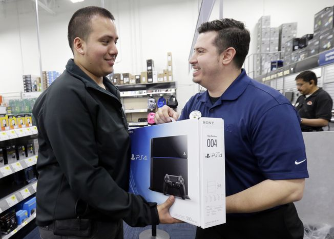 Andy Varadez, left, from Chicago, purchases a Sony PlayStation 4 from Best Buy sales manager Michael Centeno at Lincoln Park Best Buy store in Chicago on Friday, Nov. 15, 2013. The PlayStation 4, which launched Friday, and the Xbox One, which goes on sale next week, face a much-changed gaming and entertainment landscape than their predecessors. (AP Photo/Nam Y. Huh)