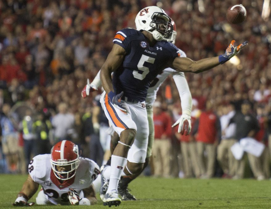 Auburn wide receiver Ricardo Louis (5) reaches out to make the catch after Georgia free safety Tray Matthews (28) and strong safety Josh Harvey-Clemons (25) bobble the interception late in the fourth quarter of an NCAA college football game at Jordan-Hare Stadium on Saturday, Nov. 16, 2013 in Auburn. Ala. Louis came up with the catch and ran in for the game-winning touchdown. Auburn won 43-38. (AP Photo/Opelika-Auburn News, Albert Cesare)