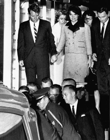 ** FILE ** In this Friday, Nov. 22, 1963, file photo, Jacqueline Kennedy, with bloodstains on her clothes, holds hands with her brother-in-law, Attorney General Robert Kennedy, as the coffin carrying the body of President John F. Kennedy is placed in an ambulance after arriving at