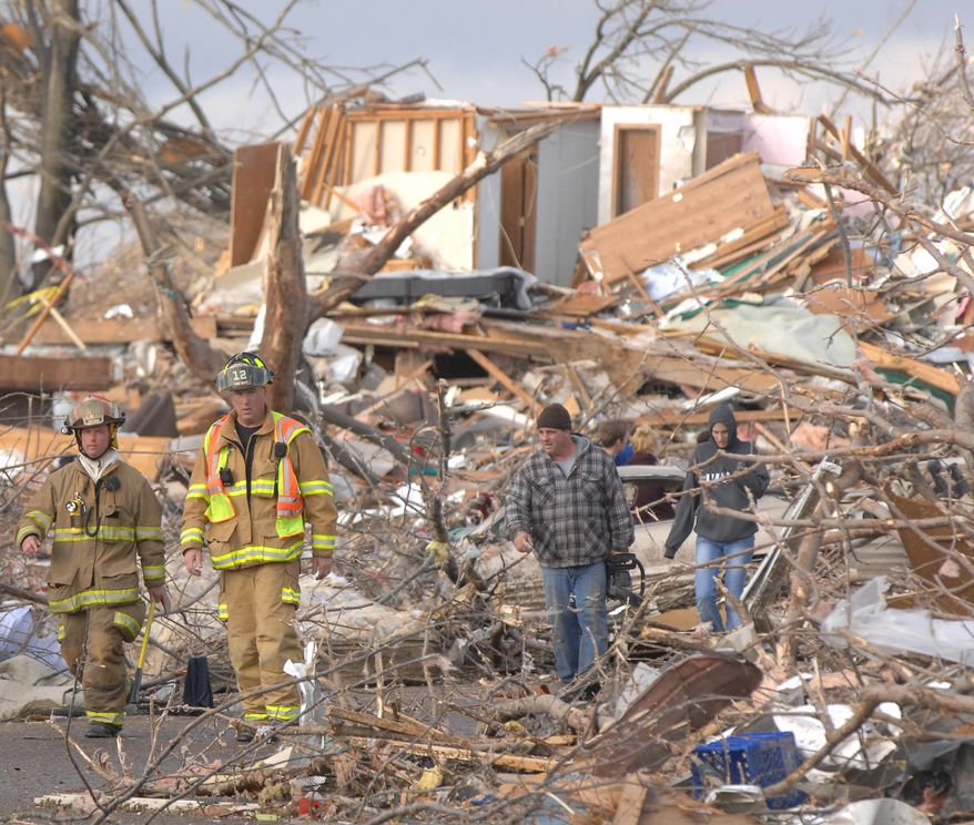 Washington firefighters survey Devonshire Street on the North side of Washington, Ill., Sunday, Nov. 17, 2013. Intense thunderstorms and tornadoes swept across the Midwest, causing extensive damage in several central Illinois communities while sending people to their basements for shelter. (AP Photo/The Pantagraph, Steve Smedley)
