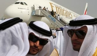 Emirati officials greet one another in front of an Emirates Airbus A380 on display on the opening day of the Dubai Airshow in Dubai, United Arab Emirates, on Sunday Nov. 17, 2013. The airshow is seen as an increasingly important barometer on the state of the industry and the rising roles of the big-spending Gulf carriers Etihad, Qatar Airways and Emirates as they compete for routes and critical stopover traffic between Asia and Europe and the Americas. (AP Photo/Kamran Jebreili)