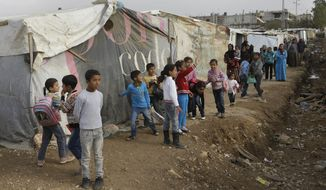 ** FILE ** Displaced Syrian children wait outside their tents for the arrival of French President Francois Hollande's companion, Valerie Trierweiler, during her visit to one of the refugee camps at Delhamiyeh village in the Bekaa Valley of eastern Lebanon on Tuesday, Nov. 5, 2013. (AP Photo/Hussein Malla)