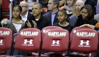 United States President Barack Obama sits behind the Oregon State bench with daughters Malia, from left, Sasha and first lady Michelle Obama before an NCAA college basketball game against Maryland in College Park, Md., Sunday, Nov. 17, 2013. Obama's brother-in-law is Oregon State head coach Craig Robinson. (AP Photo/Patrick Semansky)