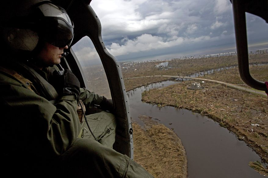 A crew member of a U.S. Navy Seahawk helicopter from the aircraft carrier USS George Washington looks at the devastation caused by Typhoon Haiyan near the coastal town of Tanawan in the central Philippines on Sunday, Nov. 17. 2013. (AP Photo/Vincent Yu)