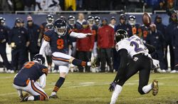 Chicago Bears kicker Robbie Gould (9) kicks the game-winning field goal in overtime to beat the Baltimore Ravens 23-20 in an NFL football game, Sunday, Nov. 17, 2013, in Chicago. Holding the ball is punter Adam Podlesh (8). At right is Ravens defensive back Chykie Brown (23).(AP Photo/Charles Rex Arbogast)