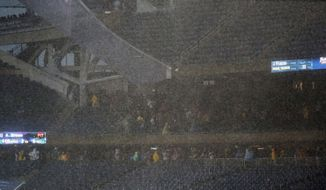 Fan seek shelter under the stands as a severe storm blows over Soldier Field during the first half of an NFL football game between the Chicago Bears and Baltimore Ravens, Sunday, Nov. 17, 2013, in Chicago. Play was suspended in the game. (AP Photo/Charles Rex Arbogast)