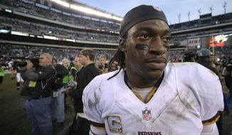 Washington Redskins quarterback Robert Griffin III walks off the field after an NFL football game against the Philadelphia Eagles in Philadelphia, Sunday, Nov. 17, 2013. The Eagles defeated the Redskins 24-16. (AP Photo/Michael Perez)