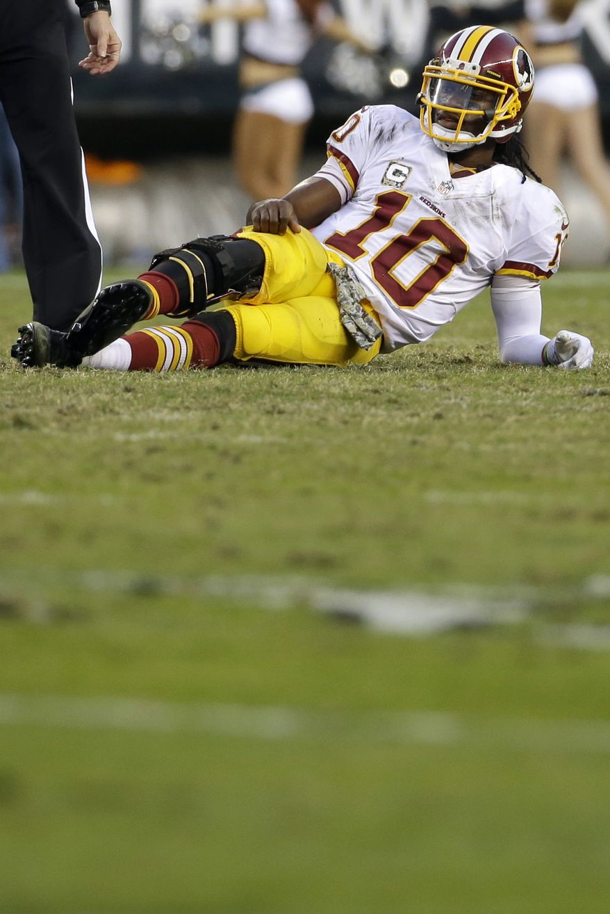 Washington Redskins quarterback Robert Griffin III lies on the field after throwing an interception during the second half of an NFL football game against the Philadelphia Eagles in Philadelphia, Sunday, Nov. 17, 2013. The Eagles defeated the Redskins 24-16. (AP Photo/Matt Slocum)