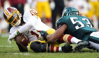 Washington Redskins quarterback Robert Griffin III is sacked by Philadelphia Eagles linebacker Najee Goode during an NFL football game in Philadelphia, Sunday, Nov. 17, 2013. (AP Photo/The News-Journal, Andre L. Smith) NO SALES