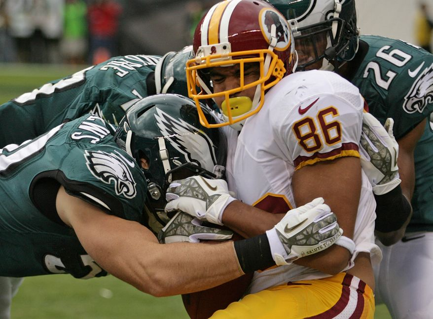 Washington Redskins tight end Jordan Reed (86) is met by several Philadelphia Eagles after catching a short pass during an NFL football game in Philadelphia, Sunday, Nov. 17, 2013. (AP Photo/The News-Journal, Andre L. Smith) NO SALES
