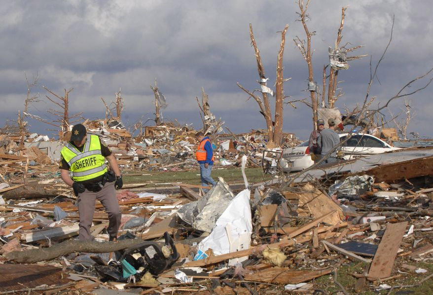 A Deputy Sergeant with the Tazewell County Sheriff's Department walks gingerly through debris in the Devonshire Subdivision in Washington, Illinois following a tornado that severely damaged many homes in the town east of Peoria on Sunday, Nov. 17,2013. (AP Photo/The Pantagraph, Steve Smedley)