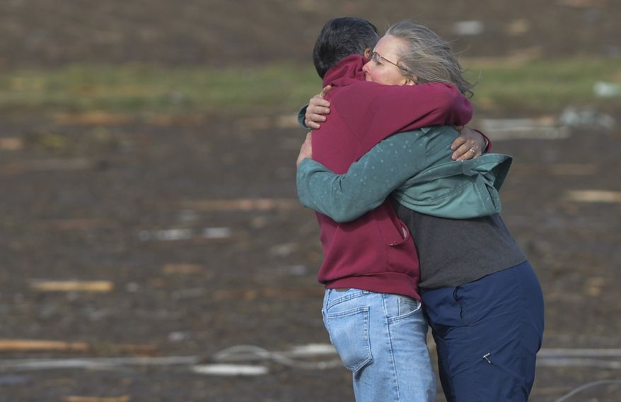 Residents embrace after they discovered their home was destroyed when a tornado and thunderstorms tore through a portion of Washington, Ill., on Sunday, Nov.17, 2013. (AP Photo/Peoria Journal Star, Ron Johnson)
