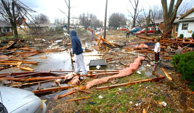 Winston Howard and son William Howard check through debree in front of their house on Meadowbrook in Cedar Crest after the tornado came through   in Kokomo, Ind., on Sunday,  Nov. 17, 2013. (AP Photo / Kokomo Tribune, Tm Bath)