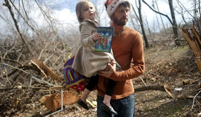 East Peoria resident Billy Vestal evacuates with his daughter, Lillian Vestal, 3, after a tornado damaged the area near Chestnut Road in East Peoria, Il.,Sunday, Nov. 17, 2013. Intense thunderstorms and tornadoes swept across the Midwest on Sunday, causing extensive damage in several central Illinois communities while sending people to their basements for shelter (AP Photo/Journal Star, Justin Wan) MANDATORY CREDIT