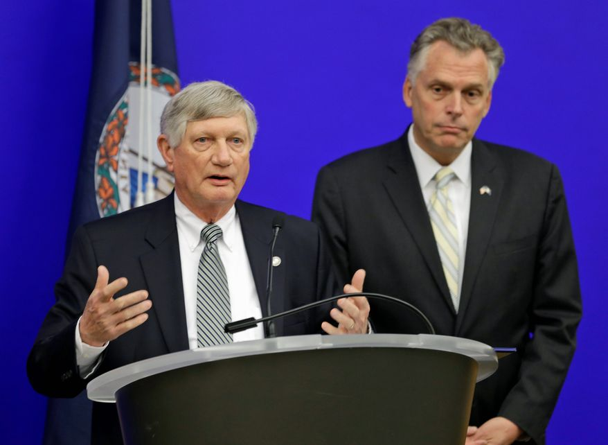 Virginia Gov.-elect Terry McAuliffe announces Monday that Secretary of Finance Ric Brown (at podium) will stay on in his administration, if only temporarily. Mr. McAuliffe also named his chief of staff, deputy chief of staff and secretary of the commonwealth. (associated press)
