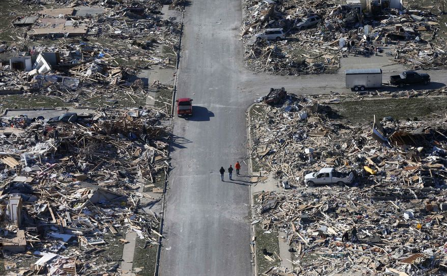 This aerial view on Monday, Nov. 18, 2013, shows people walking down a street where homes once stood that were  destroyed by a tornado that hit the western Illinois town of Washington on Sunday. It was one of the worst-hit areas after intense storms and tornadoes swept through Illinois. The National Weather Service says the tornado that hit Washington had a preliminary rating of EF-4, meaning wind speeds of 170 mph to 190 mph. (AP Photo/Charles Rex Arbogast)