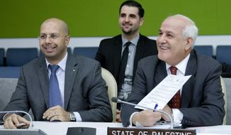 Riyad Mansour (right), permanent observer of the Palestine Authority to the United States, smiles before Palestine votes for the first time during the 53rd Plenary Meeting of the U.N. General Assembly's 68th session on Monday, Nov. 18, 2013, at the United Nations headquarters. The General Assembly elected Koffi Kumelio A. Afande of Togo as a permanent judge on the International Criminal Tribunal for the Former Yugoslavia. (AP Photo/United Nations, Amanda Voisard)