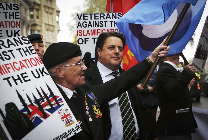 """Nick Griffin, centre chairman of the far-right, British National Party joins members of the British Veterans' Group outside the Central Criminal Court the """"Old Bailey"""" in London Monday Nov. 18, 2013,  ahead of a court hearing of Michael Adebolajo, 28, and Michael Adebowale, 22,  who are charged with the murder of British soldier Lee Rigby in May earlier this year. (AP Photo/Gareth Fuller/PA) UNITED KINGDOM OUT NO SALES NO ARCHIVE"""