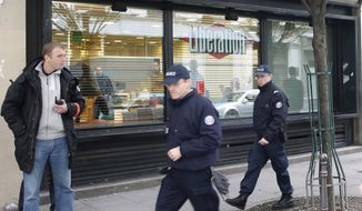 Police officers stand outside Liberation newspaper office in Paris, Monday, Nov. 18, 2013, after a gunman opened fire in the lobby, wounding a photographer's assistant before fleeing. Fabrice Rousselot, editor of the daily newspaper Liberation, said the 27-year-old victim was in serious condition. (AP Photo/Thibault Camus)