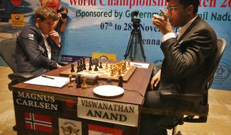 Reigning world chess champion India's Viswanathan Anand, right, takes a drink during the Chess World Championship match against Norway's Magnus Carlsen in Chennai, India, Monday, Nov. 18, 2013. (AP Photo/Arun Sankar K )