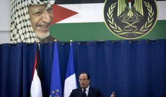 Beneath a picture of late Palestinian leaser Yasser Arafat, French President Francois Hollande talks during a joint press conference with Palestinian President Mahmoud Abbas following their meeting at the Palestinian Authority headquarters in the West Bank city of Ramallah, Monday, Nov. 18, 2013. (AP Photo/Nasser Nasser)