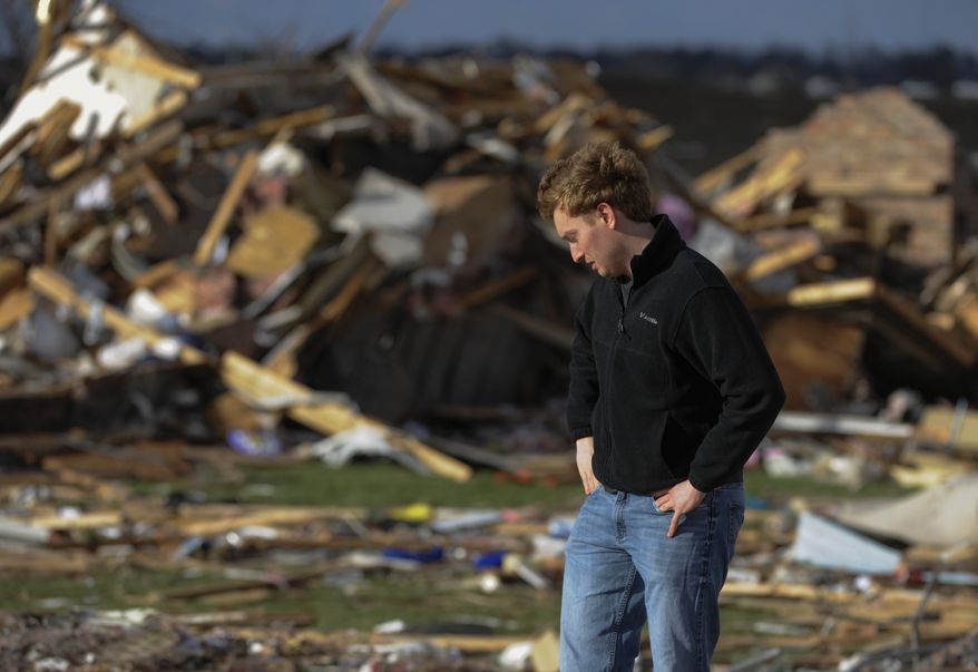 Paul Tubbs  of Washington, Ill., looks over the remains of his home on Devon Lane in Washington after a tornado tore through the north part of Washington on Sunday, Nov. 17, 2013. (AP Photo/Peoria Journal Star, Ron Johnson) MANDATORY CREDIT
