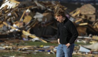 Paul Tubbs  of Washington, Ill., looks over the remains of his home on Devon Lane in Washington after a tornado tore through the north part of Washington on Sunday, Nov. 17, 2013. (AP Photo/Peoria Journal Star, Ron Johnson)