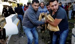 BLOODSHED: Lebanese men carry the body of a victim of explosions that struck near the Iranian Embassy in Beirut, in a stronghold of Hezbollah. (Associated Press)
