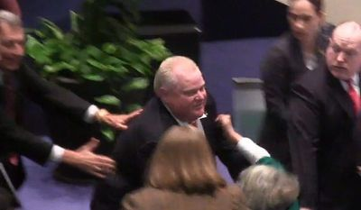 Toronto Mayor Rob Ford is shown in a video frame grab as he knocks down City Councilor Pam McConnell as he ran toward hecklers in the audience at City Hall on Monday, Nov. 18, 2013. (AP Photo/The Canadian Press, Paola Loriggio)