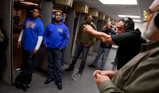 **FILE** Participants of a handgun qualification license class listen to Manager Bryon Gossard of Durwood, Md., second from right as he gives firing instructions during the live shooting portion of the class at Gilbert Indoor Range, Rockville, Md., Sunday, November 17, 2013. (Andrew Harnik/The Washington Times)
