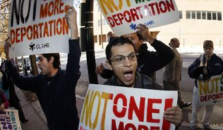 Immigration activists hold signs and shout during a protest in front of a building that houses federal immigration offices Tuesday, Nov. 19, 2013, in Atlanta.  Eight activists, protesting deportations of people who are in the country illegally, were taken into custody by police after they locked arms and some of them chained themselves to the gates outside immigration offices.  (AP Photo/John Bazemore)