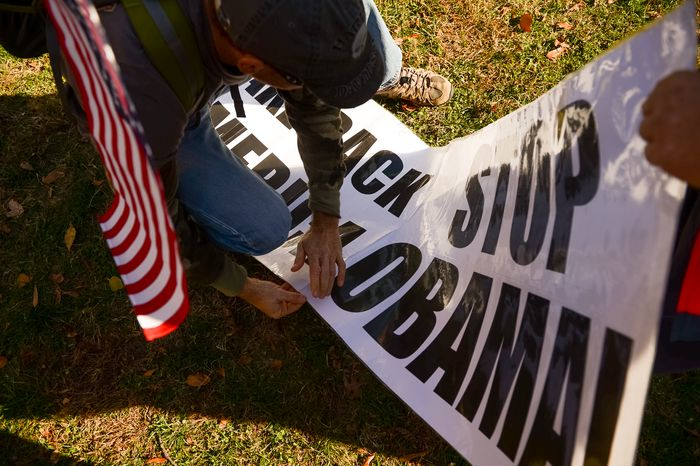 Jim and Terri of Springfield, Ill. tape a poster together as a couple dozen protesters, organized by the Reclaim America Now Coalition, gather in Lafayette Square near the White House to demand Obama's resignation, Washington, D.C., Tuesday, November 19, 2013. (Andrew Harnik/The Washington Times)