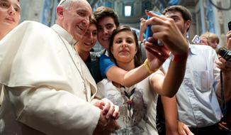 """Pope Francis poses for a """"selfie"""" with others at the Vatican. (Associated Press)"""