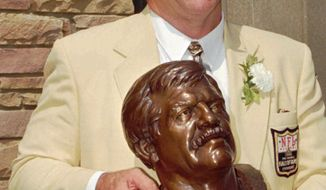 Former St. Louis Cardinals great Dan Dierdorf poses with his bust after his induction into the Pro Football Hall of Fame Saturday, July 27, 1996, in Canton, Ohio. (AP Photo/Phil Long)