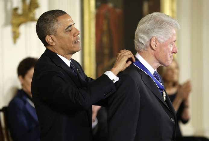 President Barack Obama awards former President Bill Clinton the Presidential Medal of Freedom, Wednesday, Nov. 20, 2013, during a ceremony in the East Room of the White House in Washington. (AP Photo/Pablo Martinez Monsivais)