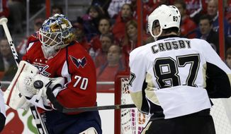 Washington Capitals goalie Braden Holtby (70) deflects a shot as Pittsburgh Penguins center Sidney Crosby (87) goes for the puck, in the second period of an NHL hockey game, Wednesday, Nov. 20, 2013, in Washington. (AP Photo/Alex Brandon)