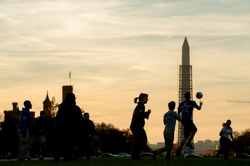 A group with Federal Emergency Management Agency (FEMA) Corps play Gator Ball, a mix of soccer and ultimate frisbee on the National Mall at sunset near their office, Washington, D.C., Wednesday, November 20, 2013. F.E.M.A. Corps is run through AmeriCorps and is devoted to disaster preparedness, response, and recovery. (Andrew Harnik/The Washington Times)