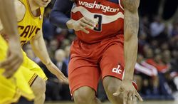Washington Wizards' Bradley Beal (3) drives past Cleveland Cavaliers' Matthew Dellavedova, from Australia, in the third quarter of an NBA basketball game on Wednesday, Nov. 20, 2013, in Cleveland. Beal scored 26 points in the Wizards' 98-91 win. (AP Photo/Mark Duncan)
