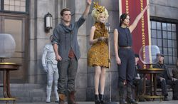"Josh Hutcherson, Elizabeth Banks (center) and Jennifer Lawrence are back for more ""Hunger Games"" in a fiery sequel cooked up for adolescent appetites. (Lionsgate via Associated Press)"