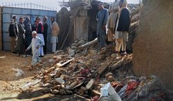 Muslim students stand in the rubble of an Islamic seminary that was hit by a suspected U.S. drone strike in Hangu district in Pakistan on Thursday. If confirmed, the missile strike outside of the northwest tribal areas would be a rarity. (Associated Press)